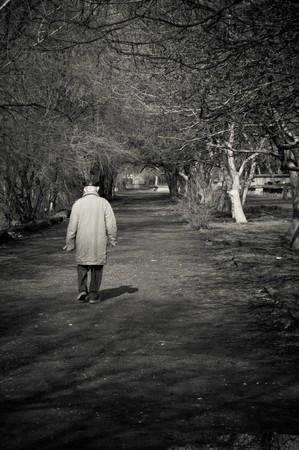 老人は一人で公園を通って行きます。黒と白の写真