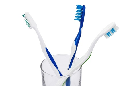 Closeup image of three toothbrushes in a glass, isolated on white background