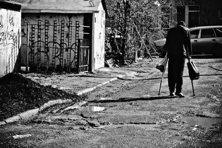 通りを歩いて松葉杖で病気の貧乏人。リアビュー;黒と白 写真素材