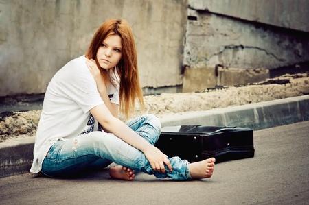 mirada triste: Hermosa joven sentada sobre asfalto
