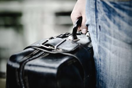 maletas de viaje: Primer plano la imagen de una mano agarrando el caso Foto de archivo