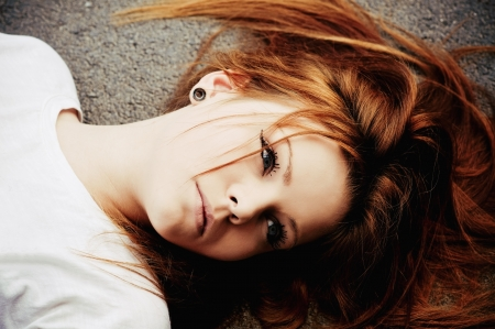 Closeup portrait of beautiful young girl lying on asphalt Stock Photo - 9968560