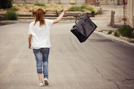 mujer de espaldas: Joven lanza su maleta caminando por la calle. Vista trasera Foto de archivo