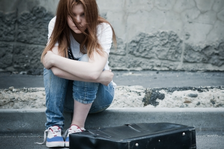 beautiful sad: Beautiful young sad girl sitting on asphalt. Photo in cold faded tones