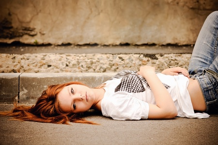Beautiful young girl lying on the street