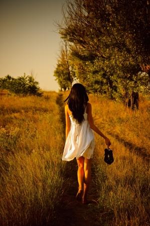 Het barefoot meisje in witte jurk met schoenen in hand is op het veld. Achterzicht Stockfoto