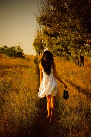 The barefoot girl in white dress with shoes in hand is on the field. Rear view Archivio Fotografico