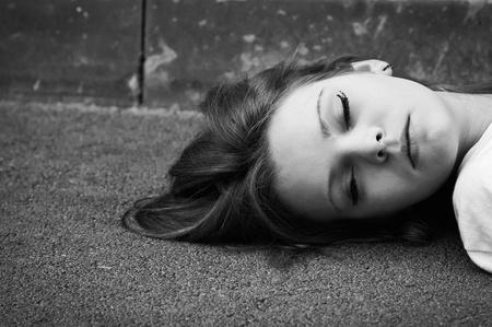 アスファルトの上に横たわって寝ている若い女の子のクローズ アップの肖像画。黒と白の写真