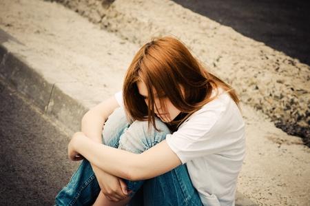 personas tristes: Hermosa joven triste sentado sobre asfalto