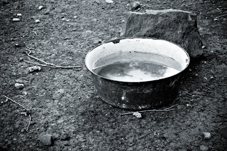 An old basin full of water standing on the ground. Black and white photo photo