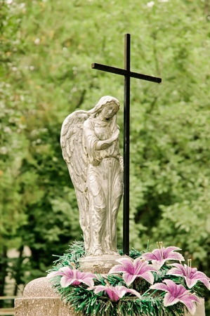 Graveyard monument: crying angel and cross photo