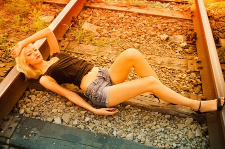 Beautiful young girl lying on the rails