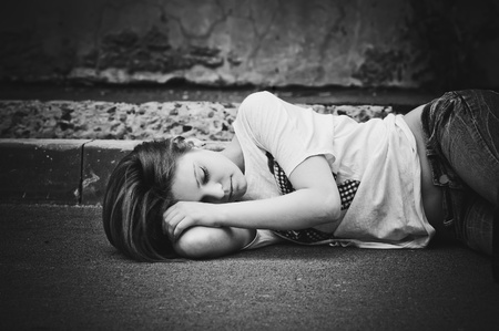 head down: Portrait of sleeping young girl on asphalt. Black and white photo