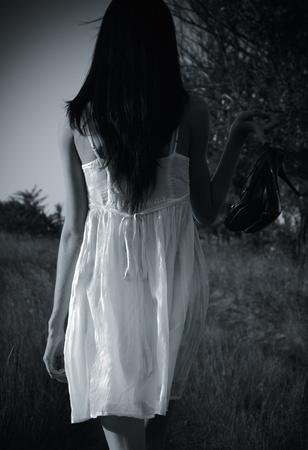 De vreemde mysterieuze meisje in witte jurk met schoenen in de hand is op het veld. Achterzijde, zwart-wit foto