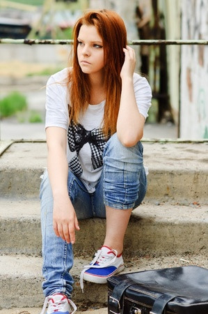 sad lonely: Beautiful young sad girl sitting on the staircase