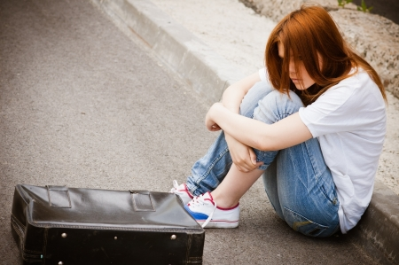 Beautiful young sad girl sitting on the asphalt Stock Photo