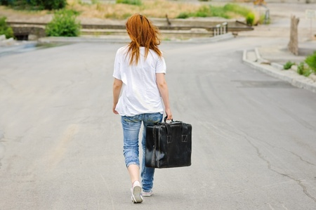 leaving: Young girl with old suitcase walking down the street. Rear view Stock Photo