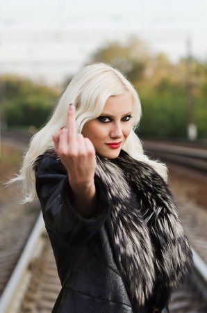 Seductive young girl showing middle finger (the fuck off gesture) photo