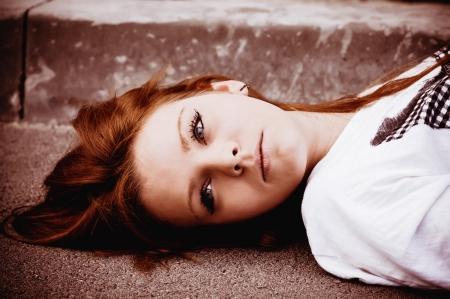 femme triste: Closeup portrait d'une jeune fille triste couch� sur l'asphalte