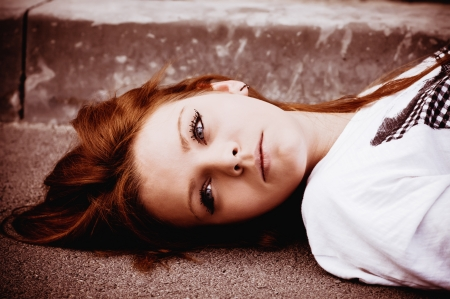 red head girl: Closeup portrait of a young sad girl lying on asphalt