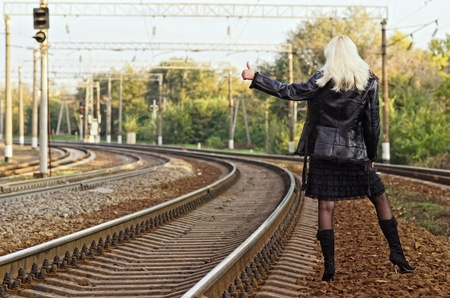 Beautiful young girl is hitch hiking on a railroad photo