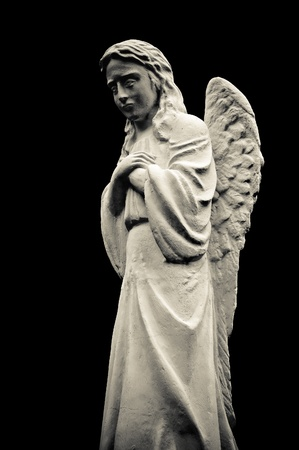 angelic: Statue of a crying angel, isolated on black background. Black and white Stock Photo