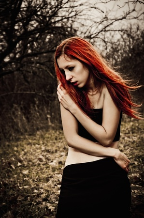 Portrait of a beautiful redhead sad girl among the autumn trees photo