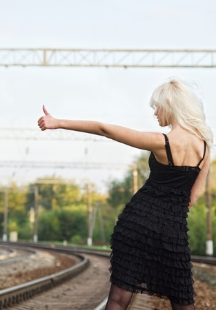 Sexy young girl in black dress is hitchhiking on a railroad  Rear view Stock Photo - 12504007