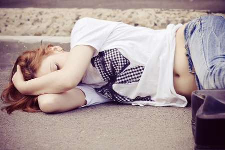 Portrait of young girl sleeping on asphalt