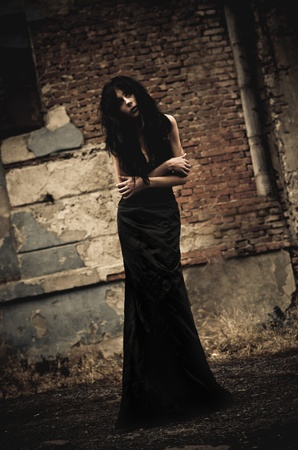 Gloomy portrait of a sick goth girl among the ruins  Low key photo