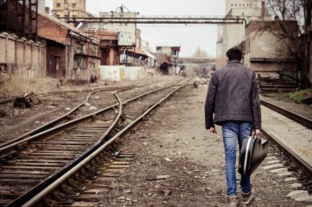 産業廃墟手のギターケースを持つ若い男が行ってしまう 写真素材