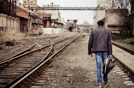 hombre solo: Hombre joven con el estuche de la guitarra en la mano se va entre las ruinas industriales Foto de archivo