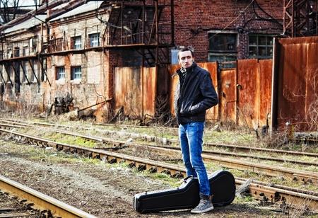 guitar case: Hombre joven con el estuche de la guitarra esperando que el tren entre las ruinas industriales Foto de archivo