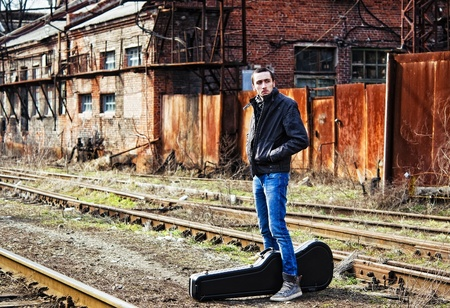 industrial ruins: Young man with guitar case waiting for the train among industrial ruins
