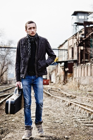 outcast: Young musician with guitar case in hand is going among industrial ruins