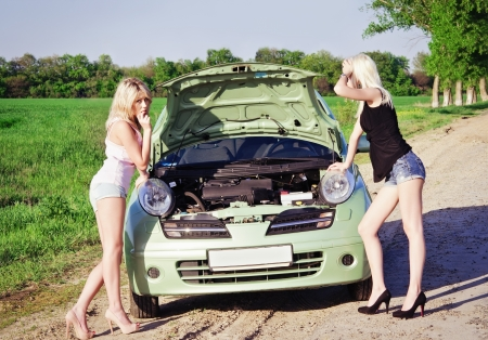 car trouble: Two sexy blonde girls stand by the broken car and don Stock Photo