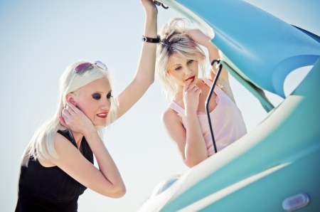 Two blonde girls stand by the broken car and don