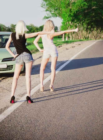 Road scene  two sexy blonde girls standing near their broken car and hitchhiking  Rear view photo
