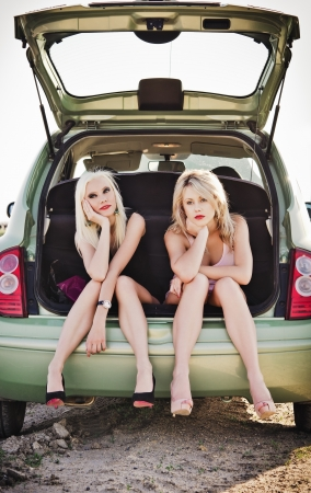 Two beautiful blonde girls sitting in a trunk of broken car and waiting for help photo