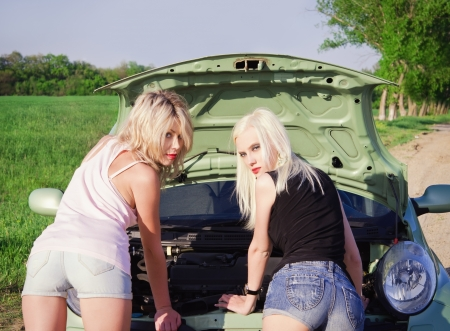 Two sexy blonde girls stand by the broken car and don photo