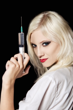 Smiling beautiful young girl in the image of nurse with syringe in hand  Closeup photo