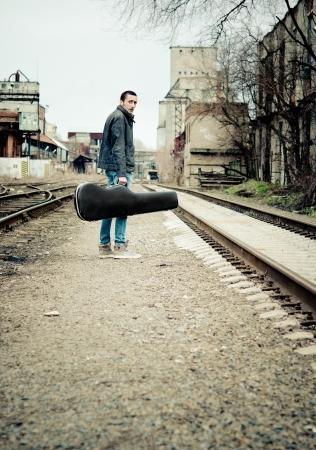 手のギターケースを持つ若い音楽家は離れて後姿を探しています 写真素材