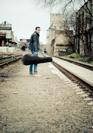 Young musician with guitar case in hand is looking away  Rear view photo