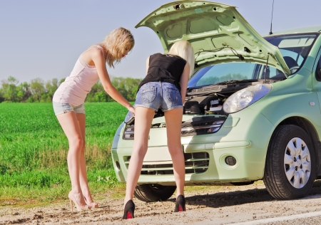 Two blonde girls standing by the broken car and trying to repair it