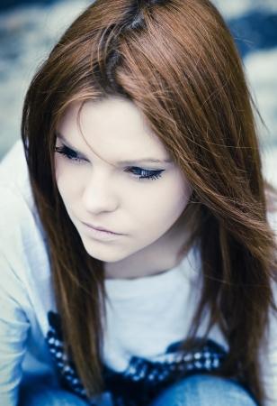 冷たいトーンの美しい悲しい少女のクローズ アップの肖像画