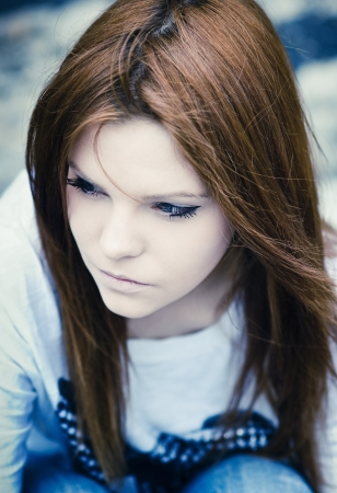 Closeup portrait of beautiful young sad girl in cold tones