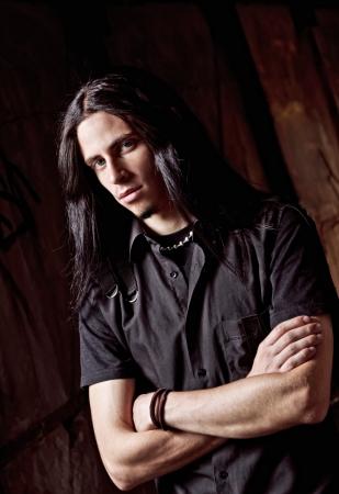 長い髪のハンサムな若い男のクローズ アップの肖像画