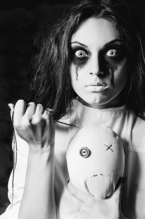 Horror scene  strange crazy girl with moppet doll and needle in hands  Closeup, black and white photo