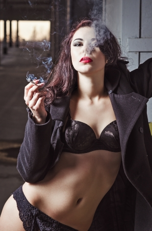 Closeup portrait of sexy smoking young girl in black underwear and coat