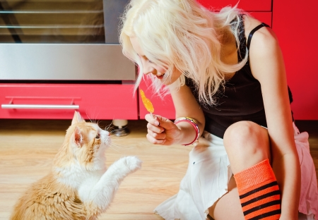 Beautiful blonde girl with candy in hand and cat sitting on a kitchen floor photo